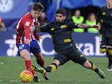 Luciano Vietto is tackled by Ever Banega during the La Liga match between Atletico Madrid and Sevilla on January 24, 2016