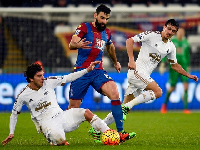 Mile Jedinak is tackled by Alberto Paloschi during the Premier League match between Swansea City and Crystal Palace at the Liberty Stadium on February 6, 2016