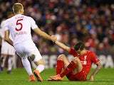 Ragnar Klavan gives Philippe Coutinho a helping hand during the Europa League game between Liverpool and Augsburg on February 25, 2016