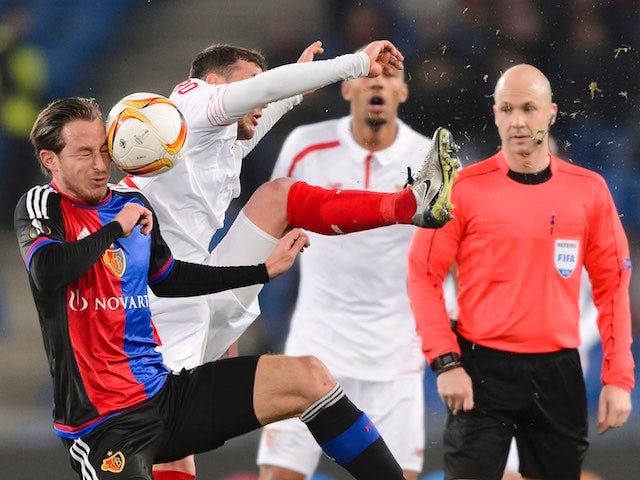 Basel's Luca Zuffi heads the ball next to Sevilla's Sebastian Cristoforo during the Europa League round of 16 first leg football match at the St Jakob Stadium on March 10, 2016