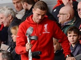 Jordan Henderson arrives on crutches in the stands during the Premier League game between Liverpool and Stoke City on April 10, 2016