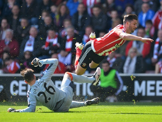 Karl Darlow tackles Shane Long during the Premier League match between Southampton and Newcastle United on April 9, 2016
