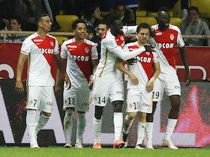 Monaco strike late to move top