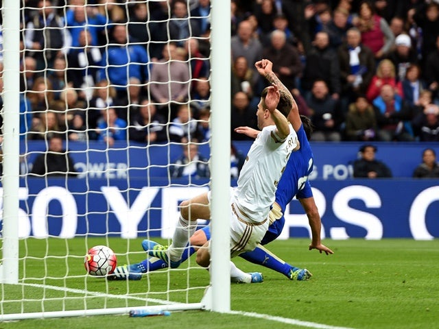 Leonardo Ulloa beats Federico Fernandez of Swansea City to score his team's third goal during the Premier League match between Leicester City and Swansea City on April 24, 2016