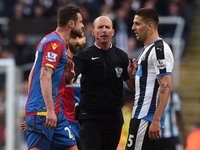 Mike Dean stunningly separates Damien Delaney and Aleksandar Mitrovic during the Premier League game between Newcastle United and Crystal Palace on April 30, 2016