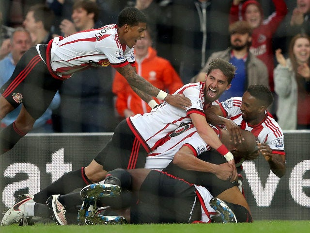 Sunderland's players pile on in celebration of their third goal during the 3-0 win over Everton at the Stadium of Light on May 11, 2016