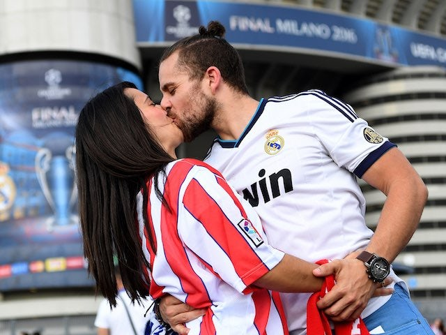A heterosexual embrace between fans of rival sides, a modern-day depiction of Romeo and Juliet, occurs prior to the Champions League final between Real Madrid and Atletico Madrid on May 28, 2016