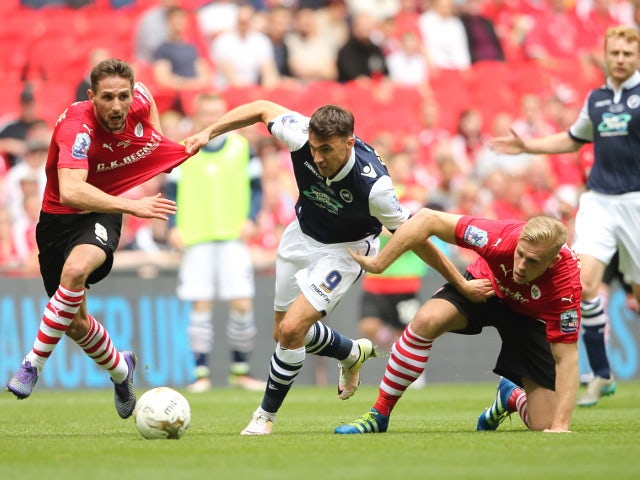 Millwall's Lee Gregory holds off the challenges of two Barnsley players during the League One playoff final at Wembley on May 29, 2016