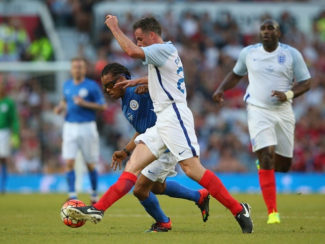 Edgar Davids of Rest of the World is tackled by Jamie Carragher of England during the Soccer Aid 2016 match in aid of UNICEF at Old Trafford on June 5, 2016