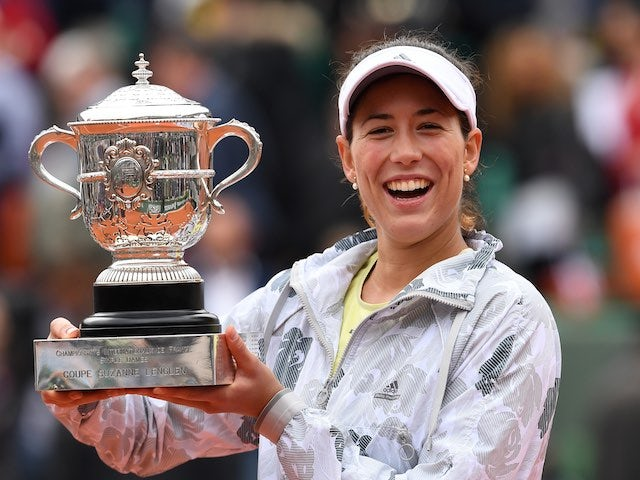 An agape Garbine Muguruza poses with the trophy after winning the French Open on June 4, 2016