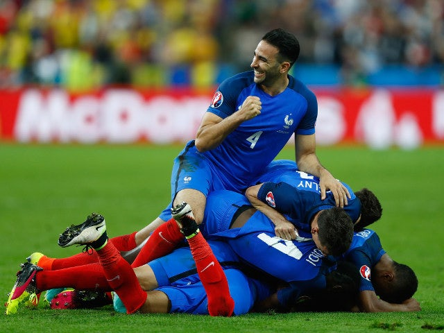 Adil Rami (top) and French players celebrate their team's second goal scored by Dimitri Payet (obscured) during the UEFA Euro 2016 Group A match between France and Romania at Stade de France on June 10, 2016 in Paris, France