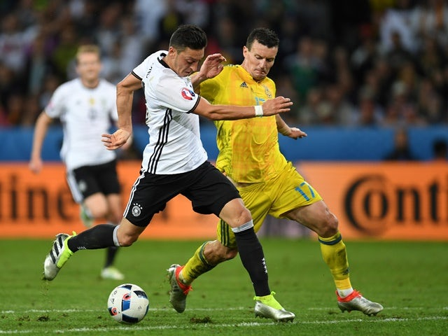 Mesut Ozil vies with Artem Fedetskiy during the Euro 2016 Group C match between Germany and Ukraine on June 12, 2016