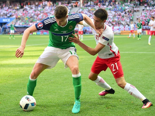 Northern Ireland's defender Paddy McNair controls the ball as Poland's Bartosz Kapustka marks him on June 12, 2016
