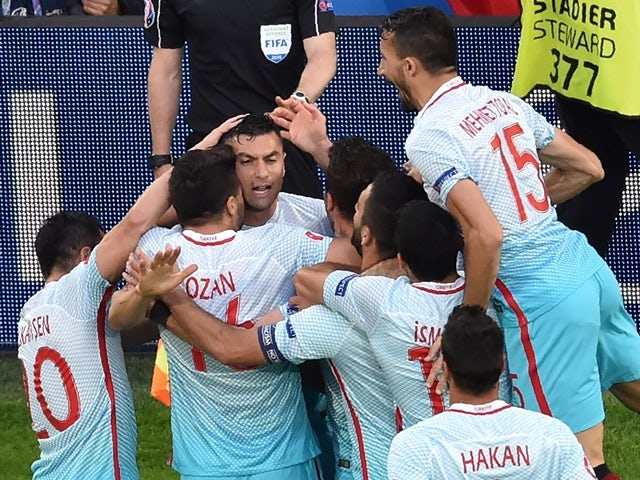 Burak Yilmaz is congratulated by teammates after scoring a goal during the Euro 2016 group D football match between Czech Republic and Turkey on June 21, 2016