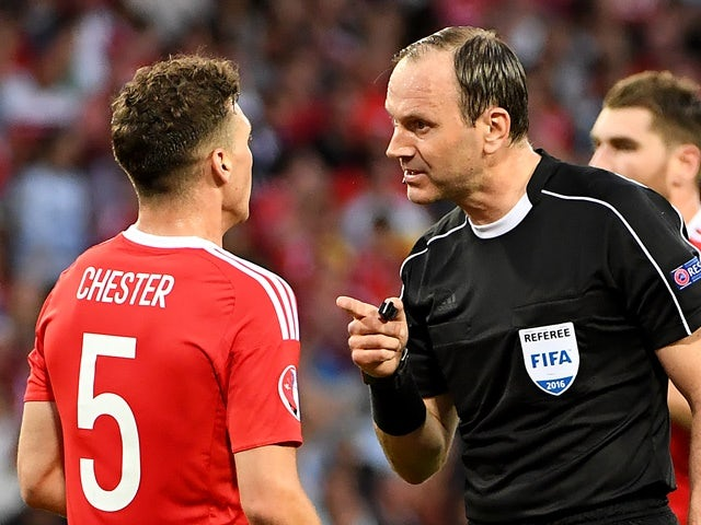 Referee Jonas Eriksson speaks to James Chester during the Euro 2016 Group B match between Russia and Wales on June 20, 2016