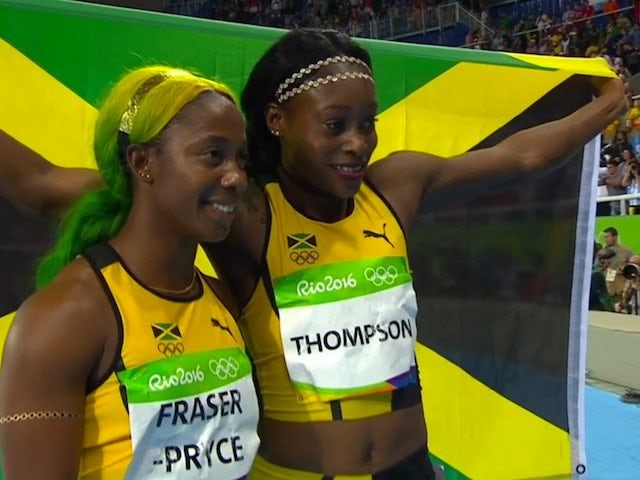 Shelly-Ann Fraser-Pryce and Elaine Thompson pose with the Jamaican flag after the women's 100m final on August 13, 2016