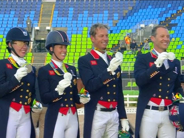 Watched on by their respective horses, Team GB's dressage team celebrate winning silver at the Rio Olympics on August 12, 2016