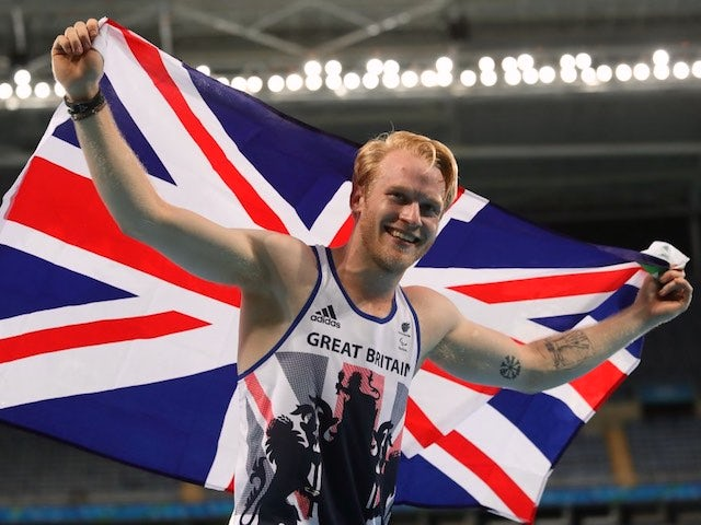 Jonnie Peacock poses with the GB flag after winning gold in the men's T44 100m final at the Rio Paralympics on September 9, 2016