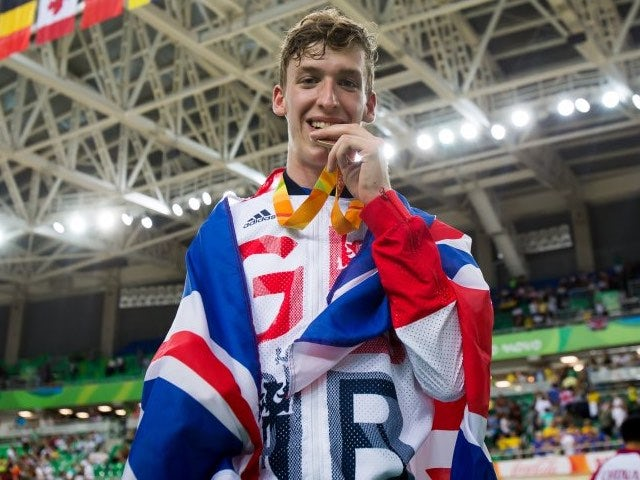 Louis Rolfe poses with his bronze medal and the GB flag after the men's C2 3000m pursuit event at the Paralympic Games in Rio de Janeiro on September 9, 2016