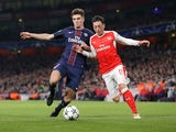 Thomas Meunier and Mesut Ozil in action during the Champions League game between Arsenal and PSG on November 23, 2016