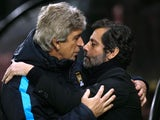 Manuel Pellegrini and Quique Flores rub noses during the game between Watford and Man City on January 2, 2016