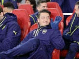 Mesut Ozil looks relaxed on the bench during the Champions League game between Arsenal and Bayern Munich on March 7, 2017