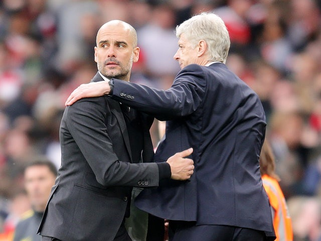 Pep Guardiola distractedly hugs Arsene Wenger after the Premier League match between Arsenal and Manchester City on April 2, 2017