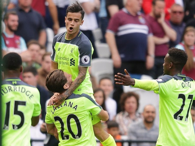 Adam Lallana hoists up Philippe Coutinho after he bags a second during the Premier League game between West Ham United and Liverpool on May 14, 2017