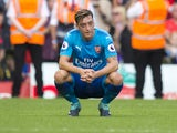 Mesut Ozil sits dejected during the Premier League game between Liverpool and Arsenal on August 27, 2017