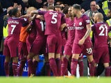 Kevin De Bruyne is mobbed by teammates after scoring during the Premier League game between Chelsea and Manchester City on September 30, 2017