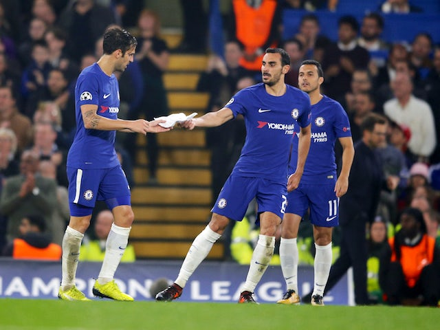 Davide Zappacosta hands a written note from Antonio Costa to Cesc Fabregas during the Champions League group game between Chelsea and Roma on October 18, 2017