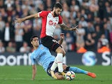 Mikel Merino tackles Charlie Austin during the Premier League game between Southampton and Newcastle United on October 15, 2017