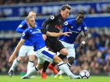 Nikola Vlasic and Idrissa Gueye take on Mesut Ozil during the Premier League game between Everton and Arsenal on October 22, 2017