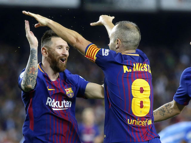 Andres Iniesta celebrates with Lionel Messi after scoring during the La Liga game between Barcelona and Malaga on October 21, 2017