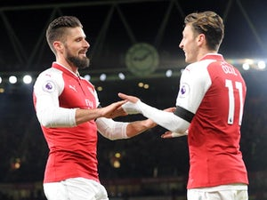 Olivier Giroud celebrates with Mesut Ozil during the Premier League game between Arsenal and Huddersfield Town on November 29, 2017