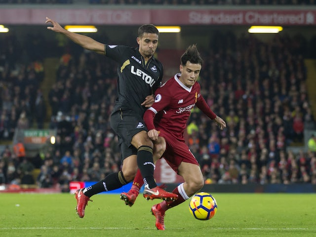 Phillipe Coutinho battles with Kyle Naughton during the Premier League game between Liverpool and Swansea City on December 26, 2017