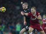 Ragnar Klavan takes on a terrified Oliver McBurnie during the Premier League game between Liverpool and Swansea City on December 26, 2017