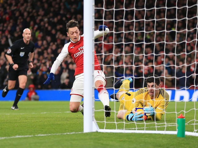 Thibaut Courtois thwarts Mesut Ozil after Alexis Sanchez's rebound during the Premier League game between Arsenal and Chelsea on January 3, 2018