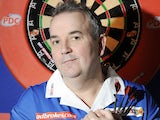 Phil 'The Power' Taylor posing up against a dartboard in late 2009