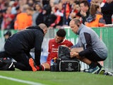 Alex Oxlade-Chamberlain sits injured during the Champions League semi-final game between Liverpool and Roma on April 24, 2018
