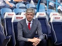 Arsene Wenger takes his seat in the dugout ahead of the Premier League game between Huddersfield Town and Arsenal on May 13, 2018