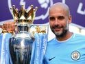 Manchester City manager Pep Guardiola poses with the Premier League trophy on May 6, 2018