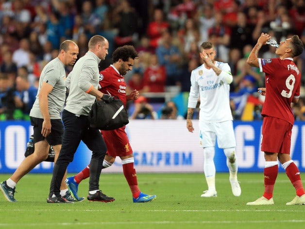 Injured Liverpool forward Mohamed Salah leaves the field during the Champions League final against Real Madrid