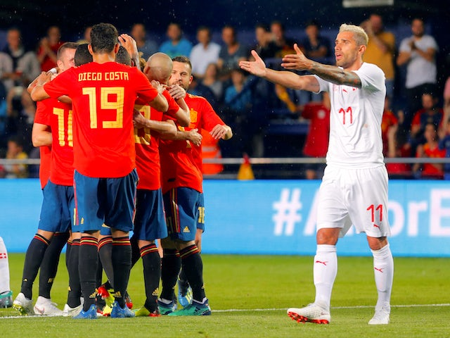 Spain's Alvaro Odriozola celebrates scoring their first goal with teammates as Switzerland's Valon Behrami reacts