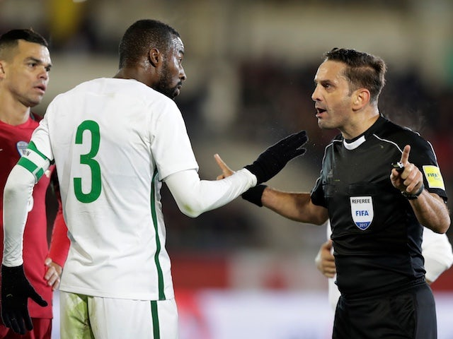 Saudi Arabia's Osama Hawsawi talks to referee Sebastian Coltescu during his side's international friendly with Portugal in November 2017
