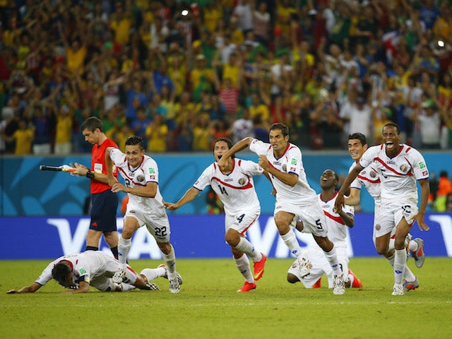 Costa Rica's players celebrate qualifying for the quarter-finals of the 2014 World Cup