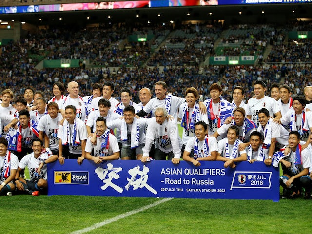 Japan's players and staff celebrate qualifying for the 2018 World Cup