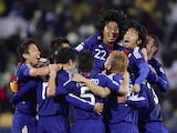 Japan's players celebrate after reaching the knockout stages of the 2014 World Cup
