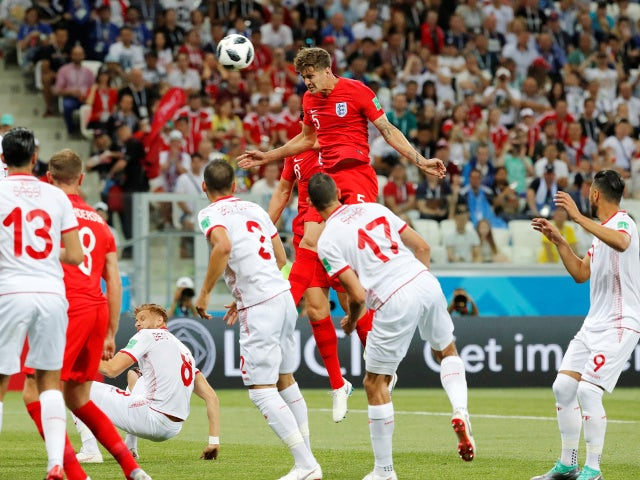England's John Stones heads at goal before Harry Kane scores their first goal from the rebound in the match against Tunisia on June 18, 2018