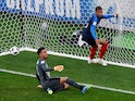 Peru's Pedro Gallese looks dejected as France's Kylian Mbappe celebrates scoring their first goal on June 21, 2018